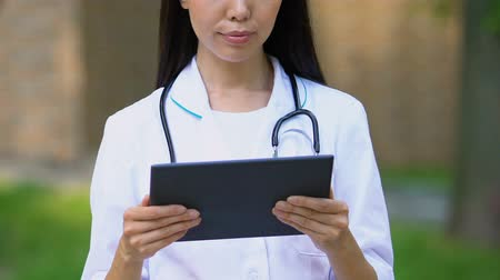 konsultant : Female therapist looking through test results of patients on tablet, online app