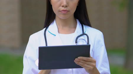 konsultant : Asian doctor checking test results in medical application on tablet, close-up