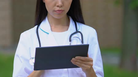 konsultant : General practitioner keeping medical records on tablet and making appointment