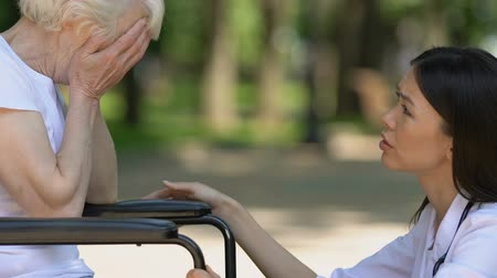 pacjent : Psychologist of nursing home supporting mature woman in wheelchair, close-up