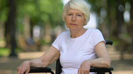 health insurance : Sad woman in wheelchair deeply sighing sitting outdoor, disability, close-up