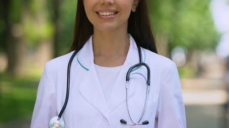 konsultant : Cheerful doctor with stethoscope smiling to camera, standing outdoor, close-up