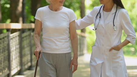 kule : Experienced doctor strolling and communicating with patient with walking cane