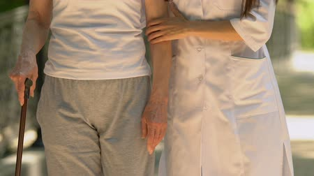 gepensioneerd : Caring nurse helping woman to move with walking stick, specializing hospital