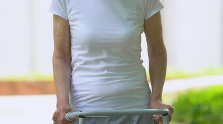 pacjent : Senior woman with walking frame smiling at camera in hospital park, recovery