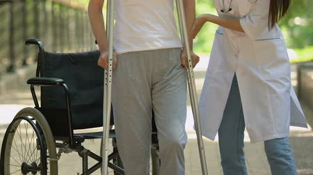 kule : Physiotherapist helping patient on wheelchair rising and walking with crutches
