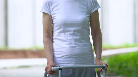 rehab : Upset senior woman with walking frame looking at camera outdoors, joint trauma
