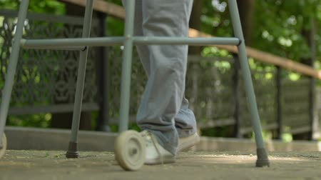 chirurgia : Hospital patient moving with walking frame in park, rehabilitation after trauma Wideo