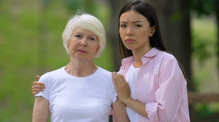 доход : Upset young woman with grandmother looking at camera outdoors, social support