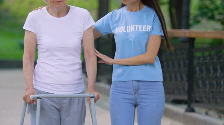pacjent : Volunteer supporting old disabled woman with walking frame, day in hospital park