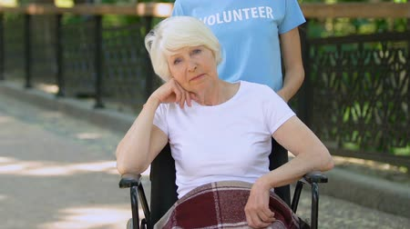 chirurgia : Volunteer with upset senior woman in wheelchair looking at camera, hospital park