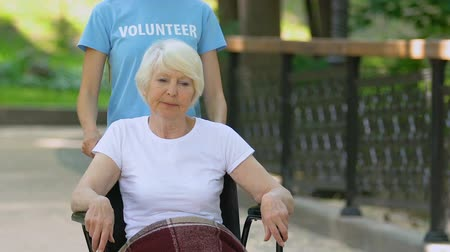 chirurgia : Volunteer helping elderly female patient in wheelchair, walking in hospital park