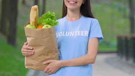 voluntary : Volunteer with food package smiling outdoors, donation for starving people