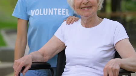 nursing : Volunteer holding hand on handicapped woman shoulder, disabled people support