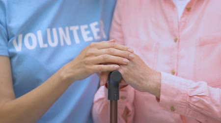 behinderte : Female volunteer stroking elderly woman hand with walking stick, health care