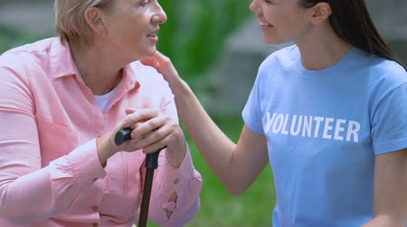 говорить : Smiling volunteer talking to senior woman with cane, togetherness, day in park
