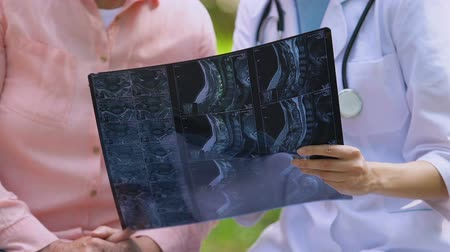 diagnóstico : Young doctor showing elderly patient joint examination x-ray result, outdoors