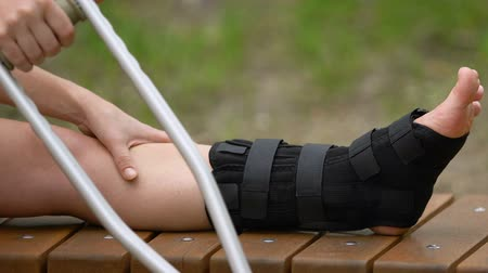 pétala : Female patient with crutches massaging painful leg in walking brace, outdoors