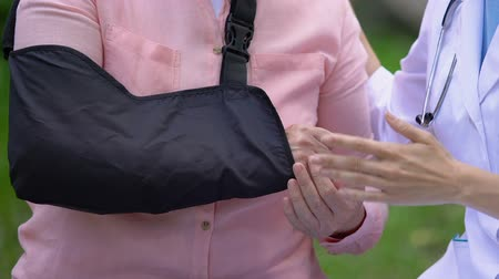 pétala : Female traumatologist consulting old patient with arm sling outdoors, treatment Stock Footage