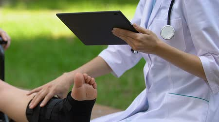 pétala : Doctor checking patient with walking brace, filling data in tablet pc, outdoors