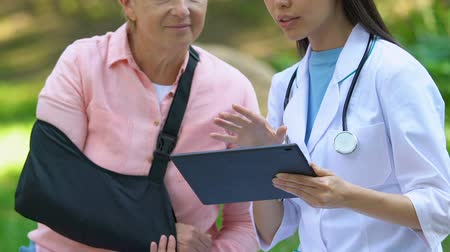 pétala : Doctor using tablet pc explaining examination result to old female in arm sling Stock Footage