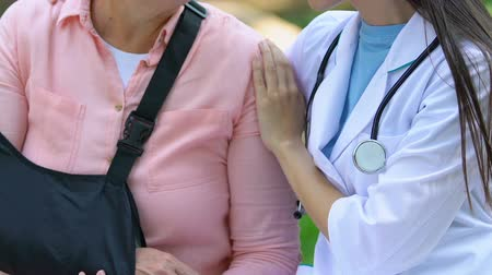 pétala : Female therapist supporting old woman in arm sling outdoors, rehabilitation Stock Footage