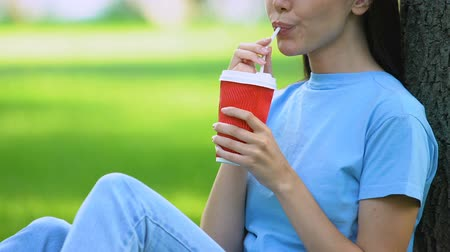 kupa : Young girl drinking coffee to go, relaxing on grass outdoors, weekend in park Stok Video