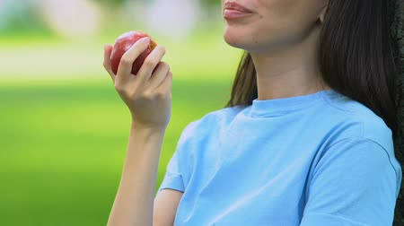 zuby : Beautiful woman eating sweet apple outdoors, healthy snack, vitamins, nutrition