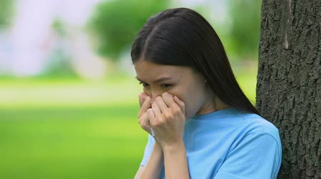 üfleme : Young woman sneezing in tissue sitting in sunny park, seasonal allergies symptom Stok Video