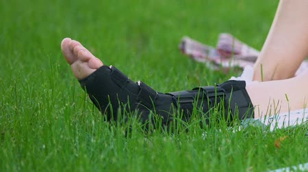 醫療保健 : Legs of woman in walking brace on grass in park, rehabilitation after injury