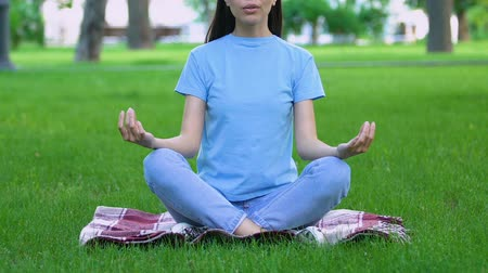дзен : Woman meditating in lotus pose, sitting on grass in park, connection with nature
