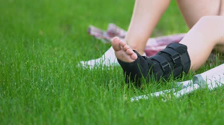pacjent : Woman sitting on grass in park, massaging painful leg in walking brace, strain