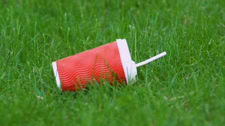 reutilizável : Plastic cup on grass in park, littering problem, human impact on environment