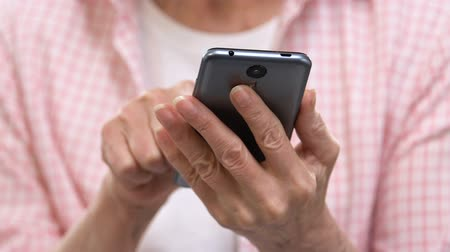 gepensioneerd : Senior woman scrolling on smartphone, application for elderly people, technology Stockvideo