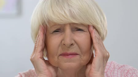 sağlıksız : Elderly female massaging temples, suffering from migraine pain, health problem