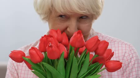 smell : Beautiful elderly woman sniffing bunch of tulips and smiling at camera, holiday