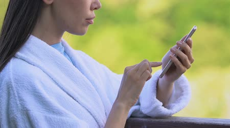 çözümler : Serious woman in bathrobe typing on smartphone outdoor, working during vacation