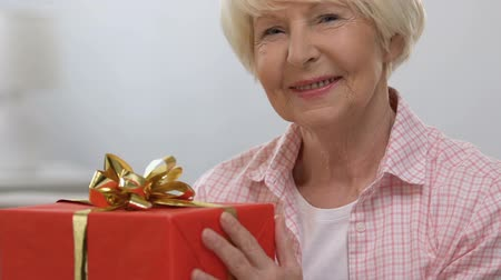 gösterileri : Happy elderly woman with red gift box smiling at camera, anniversary celebration