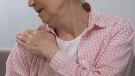 Elderly woman massaging painful shoulder, suffering from joints illness, health