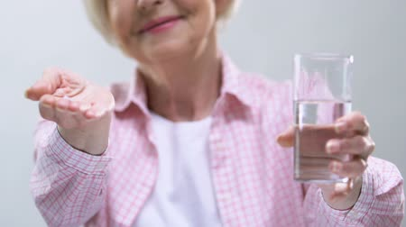 farmacologia : Smiling elderly woman showing pills and glass of water at camera, health care