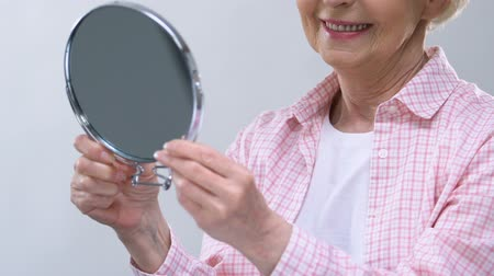 outlook : Smiling elderly woman looking in mirror, enjoying appearance, beauty care Stock Footage