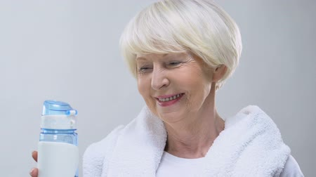 sports nutrition : Smiling old woman with towel and bottle of water, healthy lifestyle, nutrition Stock Footage
