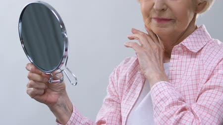 elderly care : Aged woman looking in mirror, touching wrinkled face, thinking about lost beauty