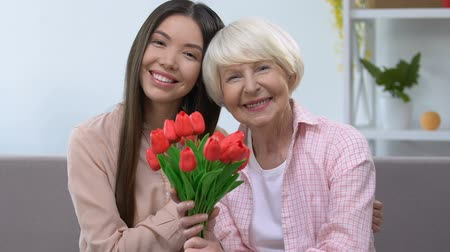 buquê : Hugging grandmother and granddaughter with bouquet of tulips looking at camera