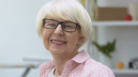 оптический : Smiling old woman in eyeglasses looking at camera, vision treatment, health care