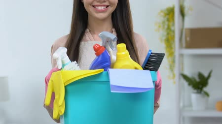 detersivo : Smiling housewife with basket of detergents looking at camera, cleaning service Filmati Stock