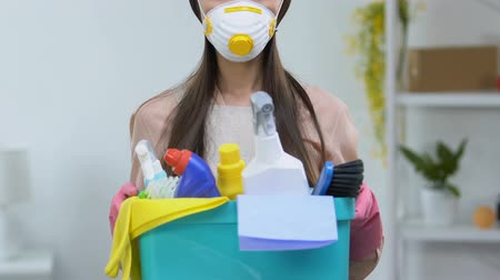 dezenfekte etmek : Housewife in respirator holding basket with detergents, dangerous chemicals Stok Video