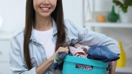 щеткой : Smiling young woman holding basket with dirty clothes, laundry service, close-up Стоковые видеозаписи