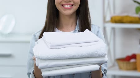têxteis : Smiling housewife showing clean white linen into camera, whitening effect Stock Footage