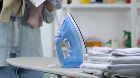 гладильный : Woman putting pile of clothes on ironing board, hard domestic work, chores Стоковые видеозаписи